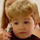 Het stileren en het snijden jonge geitjeshaar Klein kind in herenkapper Weinig jongen met blond haar bij kapper Leuke jongens stock afbeelding