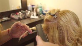 Het stileren van een cliënt` s haar in schoonheidssalon stock footage