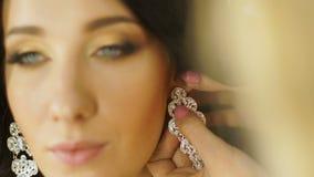 Het stilistmodel draagt oorringen in de oren stock videobeelden