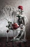 Het stilleven met antieke stoel, nam en thee toe stock foto