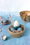 Het stilleven met blauwe paaseieren in a wattled plaat Stock Foto