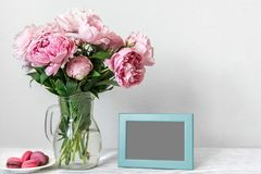 Het stilleven met boeket van roze pioen bloeit, lege fotokader en makarons Spot omhoog stock afbeelding