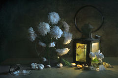 Het stilleven met een boeket van witte asters in een waterkruik water, stak een het leven licht van een oude lantaarn aan, stukke Stock Fotografie