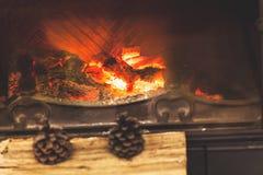 Het stilleven van de winter Twee kegels liggen op logboeken door open haard Stock Fotografie