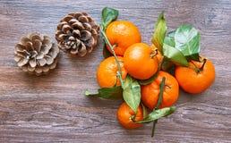 Het stilleven van de de wintervakantie van verse mandarijnen met denneappels op houten lijst Hoogste mening stock afbeelding