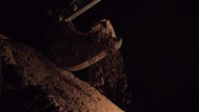 Het Stof die van graafwerktuigdigging sand and tijdens de Wegwerken bij Nacht werken, sluit omhoog Geschoten van Emmer Aardeverhu stock footage