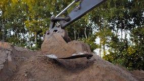 Het Stof die van graafwerktuigdigging sand and tijdens de Wegwerken werken, sluit omhoog Geschoten van Emmer van een Gravende Mac stock footage