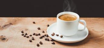 Het stomen van koffiekop op houten lijst met donkere achtergrond Stock Afbeeldingen
