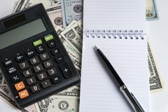 Het stootkussen van de Witboeknota en pen, calculator op usi van dollarbankbiljetten Royalty-vrije Stock Foto's