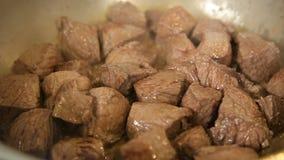 Het stoven van kubussen van rundvlees in een braadpan stock videobeelden