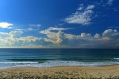 Het strand met een oceaan stormt voor de kust op de horizon stock afbeeldingen