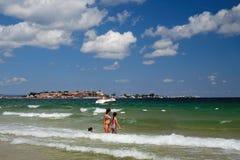 Het strand in Nessebar, Bulgarije 25 06 2018 Meisjes komen aan overzees op de achtergrond van Oude Nessebar royalty-vrije stock foto's