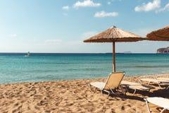 Het strand sunbed en parasol overziend turkoois water stock fotografie