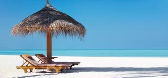 Het strand van Beautifu met stoelen en paraplu Royalty-vrije Stock Afbeeldingen