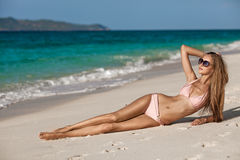 Het Strand van bronstan woman sunbathing at tropical stock foto