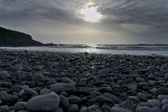 Het strand van de kiezelsteen bij zonsondergang Stock Afbeeldingen