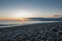 Het strand van de kiezelsteen bij zonsondergang royalty-vrije stock afbeelding