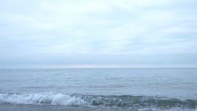 Het strand van de kiezelsteen bij zonsondergang De golven ploeteren en breken in druppeltjes 4k, langzame motie stock footage