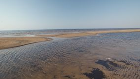 Het strand van de Oostzeegolf met wit zand in de zonsondergang - 4K-video met langzame camerabeweging en binnenstabilisatie stock videobeelden