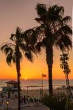 HET STRAND VAN MANHATTAN, DE V.S. - 27 MAART, 2015: Badmeestertoren bij oranje zonsondergang op 28 Maart, 2015 in het Strand van  Stock Afbeeldingen