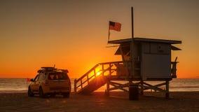 HET STRAND VAN MANHATTAN, DE V.S. - 27 MAART, 2015: Badmeestertoren bij oranje zonsondergang op 27 Maart, 2015 in het Strand van  Stock Fotografie