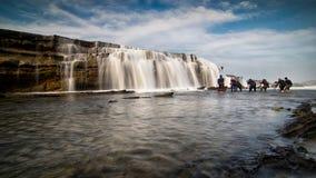 Het strand van Sawarna 25 kunnen 2016 Een groep fotografen die schot van dalend zeewater van grote rots proberen te nemen in Sawa Stock Fotografie