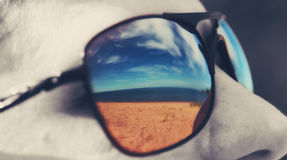 Het strand wordt weerspiegeld in zonnebril Stock Afbeeldingen