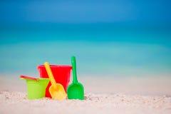 Het strandspeelgoed van het jonge geitje op wit zand Emmers en bladen voor jonge geitjes op het witte zandige strand na de spelen Stock Afbeelding