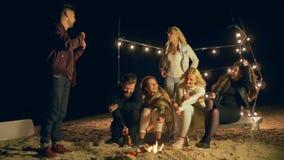 Het strandvermaak, groep Vrienden speelt in grappige spelen zittend door vuur tijdens picknick bij nacht stock footage