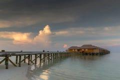 Het strandvilla's van de Maldiven in zonsonderganglandschap royalty-vrije stock afbeeldingen