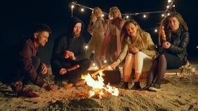 Het strandvoedsel, jongeren kookt vleesproduct bij kampvuur en dans terwijl sausvakanties op openlucht stock videobeelden