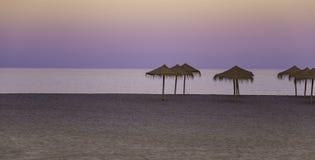 Het strandzonsondergang van MalagetaStock Afbeeldingen