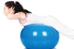 Het streching van de vrouw op de blauwe bal Stock Afbeeldingen