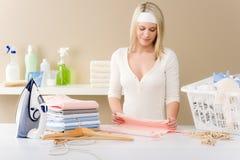 Het strijken van de wasserij - vrouw die kleren vouwt stock afbeelding