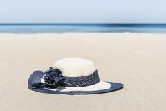 Het strohoed van vrouwen op het strand Stock Foto's