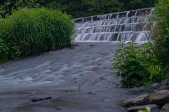 Het stromende water werd melkachtig wit door een lange blootstelling aangezien het rond groene en bruine bemoste rotsen stroomt royalty-vrije stock afbeeldingen