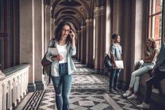 Het studentenleven Jonge vrouwelijke student die bij de universiteit en het aanpassen glazen gaan royalty-vrije stock afbeeldingen