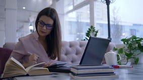 Het studentenmeisje die in oogglazen online met boeken en computerlaptop leren schrijft nota's in notitieboekje stock videobeelden
