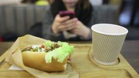 Het studentenmeisje in glazen zit met een smartphone in een koffie Een sappige smakelijke hotdog ligt in de voorgrond stock video