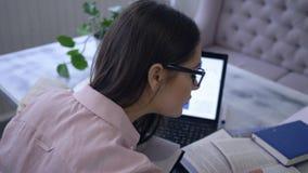Het studentenmeisje leert online lessen met boeken terwijl het zitten bij laptop in koffie tijdens e-onderwijs stock footage