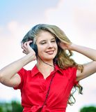 Het studentenmeisje met rugzakhoofdtelefoon luistert muziek op groen gras royalty-vrije stock fotografie