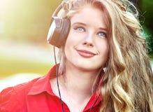 Het studentenmeisje met rugzakhoofdtelefoon luistert muziek op groen gras stock foto