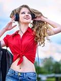 Het studentenmeisje met rugzakhoofdtelefoon luistert muziek op groen gras royalty-vrije stock afbeelding