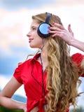 Het studentenmeisje met rugzakhoofdtelefoon luistert muziek op groen gras stock fotografie