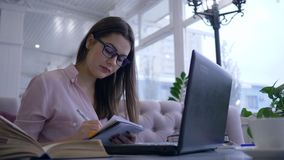Het studentenmeisje schrijft nota's zittend bij lijst met boeken en laptop in koffie tijdens e-onderwijs stock videobeelden