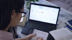 Het studentenmeisje trekt een grafiek in notitieboekjezitting bij een lijst met boeken en laptop in koffie tijdens e-onderwijs stock footage