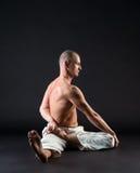 Het studiobeeld van de mens die op middelbare leeftijd yoga doen stelt Stock Afbeelding