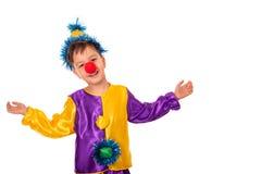 Het studioportret van een kleine jongen die Carnaval-kostuum van een clown met een rode ronde neus dragen, isoleert Hij spreidde  stock foto