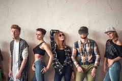 Het studioportret van zeven jonge manier aantrekkelijke glimlachende Kaukasische vrouwen en mannen vrienden kleedde samen jeansgr Stock Foto