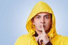 Het studioschot van geheime knappe prettige het kijken mannelijke levensonderhoudwijsvinger op lippen, vraagt geheim te houden en stock afbeelding